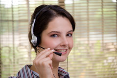 Young woman with headphones looking. Pretty woman with headphones in a telemarketing call centre Royalty Free Stock Photo