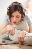 Young woman with headphones lying on the floor Stock Images