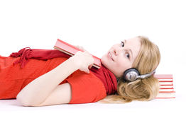 Young woman in headphones lying on heap of books Stock Image