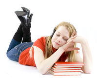 Young woman in headphones lying on heap of books Royalty Free Stock Images