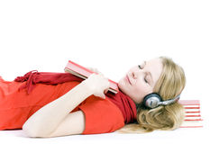 Young woman in headphones lying on heap of books Royalty Free Stock Photography
