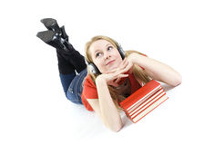 Young woman in headphones lying on heap of books Stock Photos