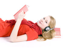 young woman in headphones lying on pile of books Stock Photo