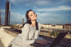 Young woman with headphones relaxing on music at laptop outdoor Stock Photo