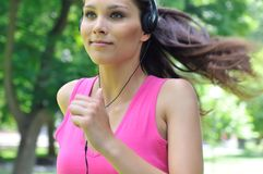Young woman with headphones running Stock Photos