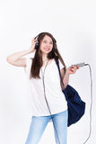 Young woman in headphones singing songs on a white background. Very young Royalty Free Stock Photo