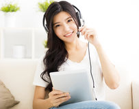 Young Woman with headphones and tablet in  living room Stock Photography