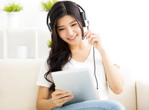 Young Woman with headphones and tablet in  living room Royalty Free Stock Photography