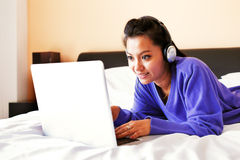 Young woman in headphones using a laptop in bed Stock Photo