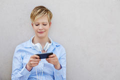 Young woman with headphones using smartphone Royalty Free Stock Image