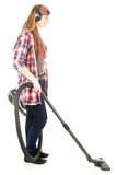 Young woman with headphones and a vacuum cleaner Stock Photos