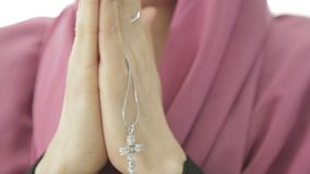 Young woman in headscarf is praying. close-up female hands holding chain with a cross. Young woman is praying. close-up female hands holding chain with a cross stock video