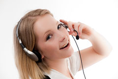 Young woman with headset. Young woman talking on headset looks embarrased or scared royalty free stock images