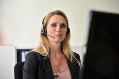 Young woman headset computer. Close up on an attractive happy young woman at a desktop with a headset and a computer Royalty Free Stock Photos