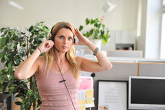 Young woman headset computer. Close up on an attractive young woman with a headset in an office Stock Images
