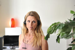 Young woman headset computer. Close up on an attractive young womanwith a headset in an office Royalty Free Stock Photography