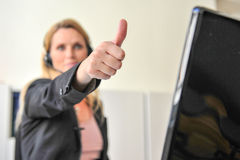 Young woman headset computer. A young woman does a thumb up for successs at a desktop with a headset and a computer Royalty Free Stock Image