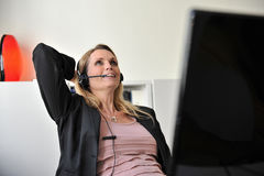 Young woman headset computer. Satisified attractive happy young woman at a desktop with a headset and a computer leaning back Stock Photo