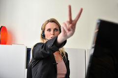 Young woman headset computer. A young woman showing victory sign for successs at a desktop with a headset and a computer Stock Photography