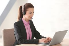 Young woman with headset and laptop working. In office Stock Images