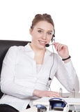 Young woman with headset is sitting at the desk Royalty Free Stock Photography