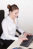Young woman with headset types at the keyboard Royalty Free Stock Images