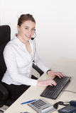 Young woman with headset types at the keyboard Royalty Free Stock Photo