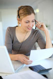 Young woman with headset working at home Royalty Free Stock Images