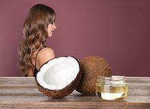 Young woman with healthy hair and natural coconut oil on wooden table. Against color background stock images