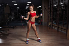 Young woman, with healthy sporty figure with skipping rope in gym Royalty Free Stock Images