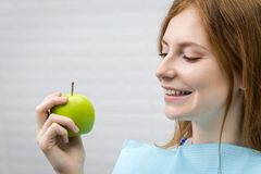 Young woman with healthy tooth biting green apple royalty free stock photography