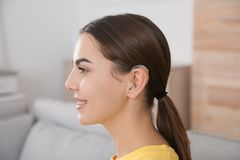 Young woman with hearing aid. At home stock photos