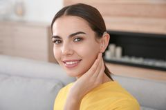 Young woman with hearing aid. At home stock image