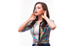 Young woman with a hearing disorder or hearing loss cupping her hand behind her ear. With her head turned aside to try and amplify and channel the available stock image