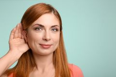 Young woman with hearing problem. On color background Royalty Free Stock Photos