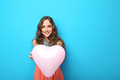 Young woman with heart balloon. Portrait of young woman with pink heart balloon on blue background royalty free stock photography