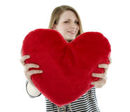Young woman with heart pillow Stock Photos