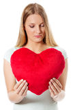 Young woman with a heart pillow in her hands - Valentines day concept. Stock Photo