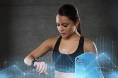 Young woman with heart-rate watch and towel in gym Royalty Free Stock Photo