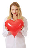 Young woman with heart shaped balloon. Royalty Free Stock Photo
