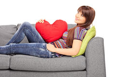 Young woman with a heart shaped pillow lying on a sofa Royalty Free Stock Images
