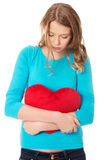 Young woman with heart shaped pillow Stock Images