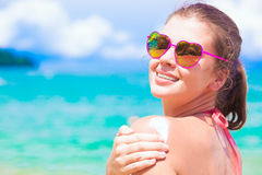 Young woman in heart shaped sunglasses putting sun cream on shoulder Stock Images