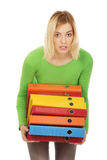 Young woman with heavy binders. Royalty Free Stock Photography