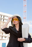 Young  woman in a helmet and by documents Royalty Free Stock Photos