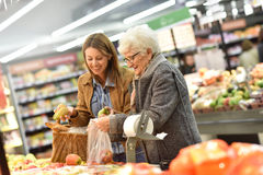 Young woman helping elederly with groceries Stock Photo