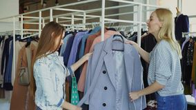 Young woman is helping her friend to find coat. She is bringing her new model, telling about it and showing its