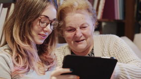 Young Woman Helping Her Grandmother For Using A Digital Tablet. Cheerful young girl with an elderly woman playing together with digital tablet at home stock footage
