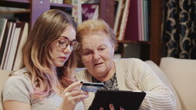 Young Woman Helping Her Grandmother For Using A Digital Tablet and credit card stock video footage