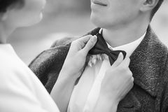 Young woman helping man with bow-tie Stock Photography